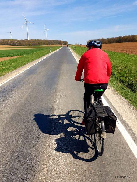 Radfahrer vor Windkraftanlagen